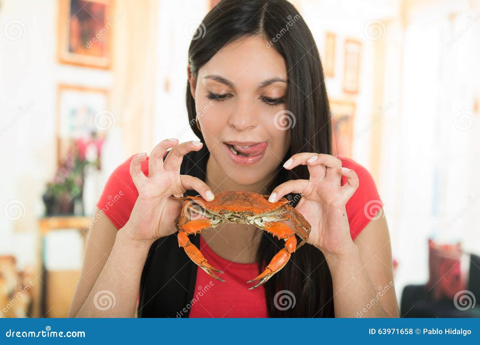 Chica joven hermosa que goza de un cangrejo delicioso