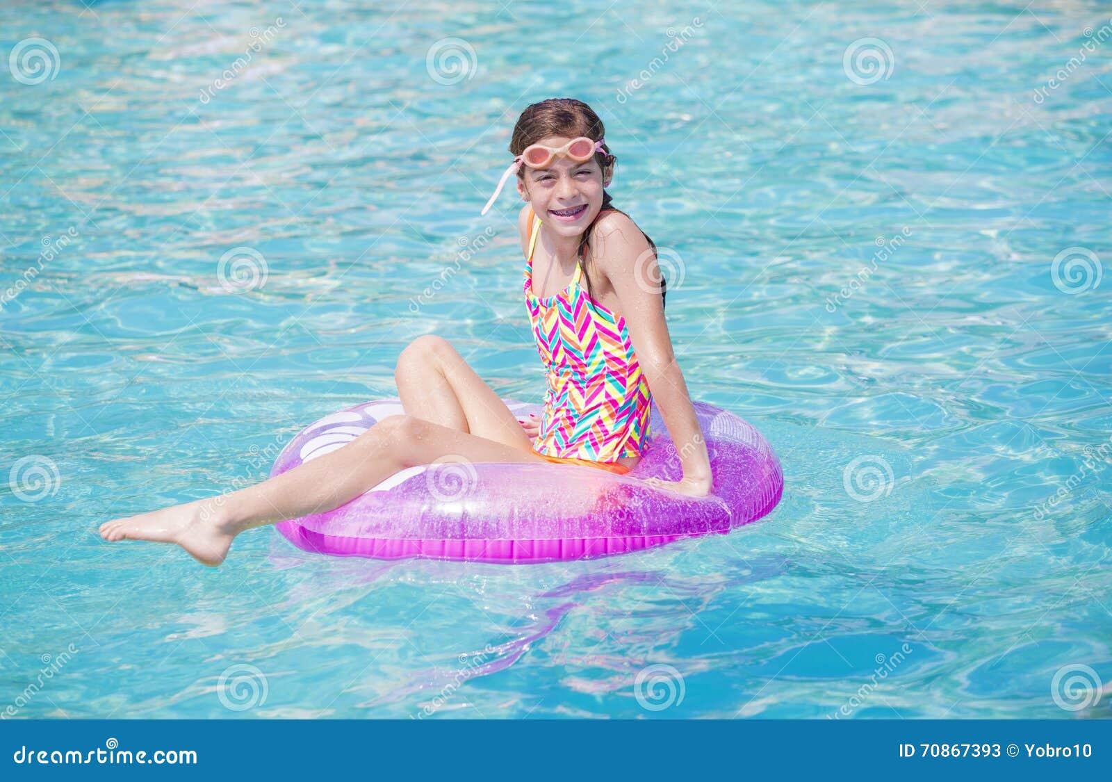 Chica joven hermosa que juega en la piscina en tiempo de verano