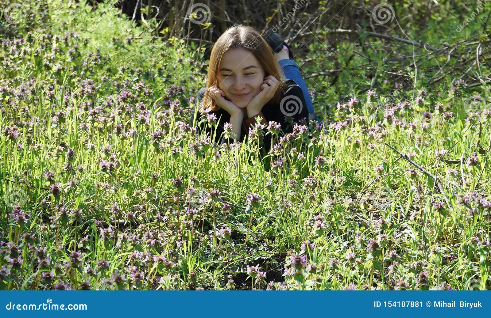 Chica joven hermosa que miente al borde del bosque, viviendo con la naturaleza