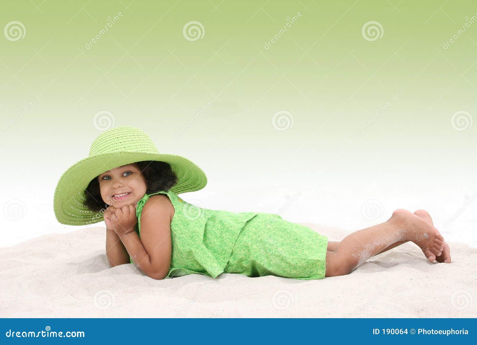 Chica joven hermosa que pone en la arena que desgasta el sombrero verde grande