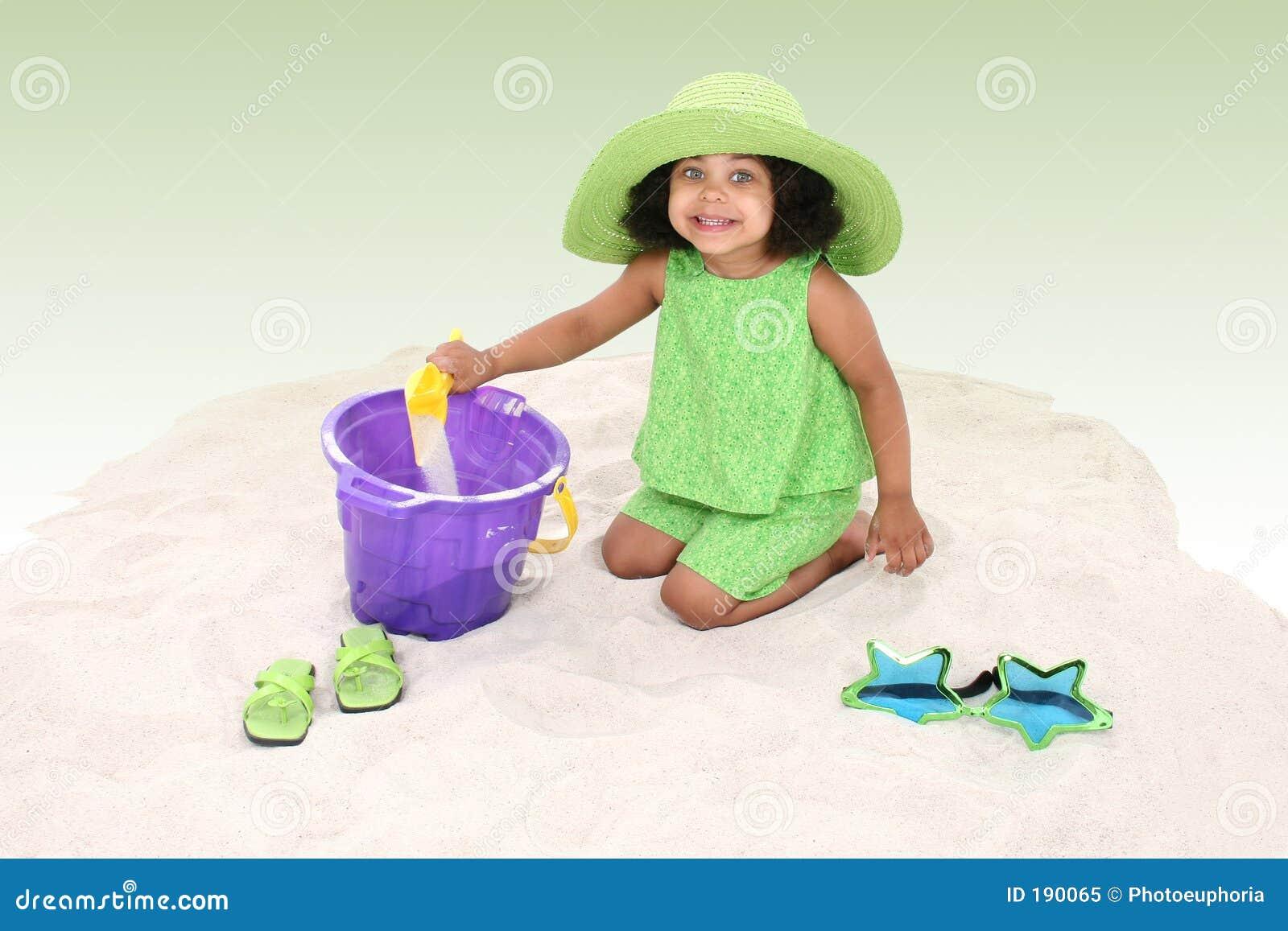 Chica joven hermosa que se sienta en jugar de la arena