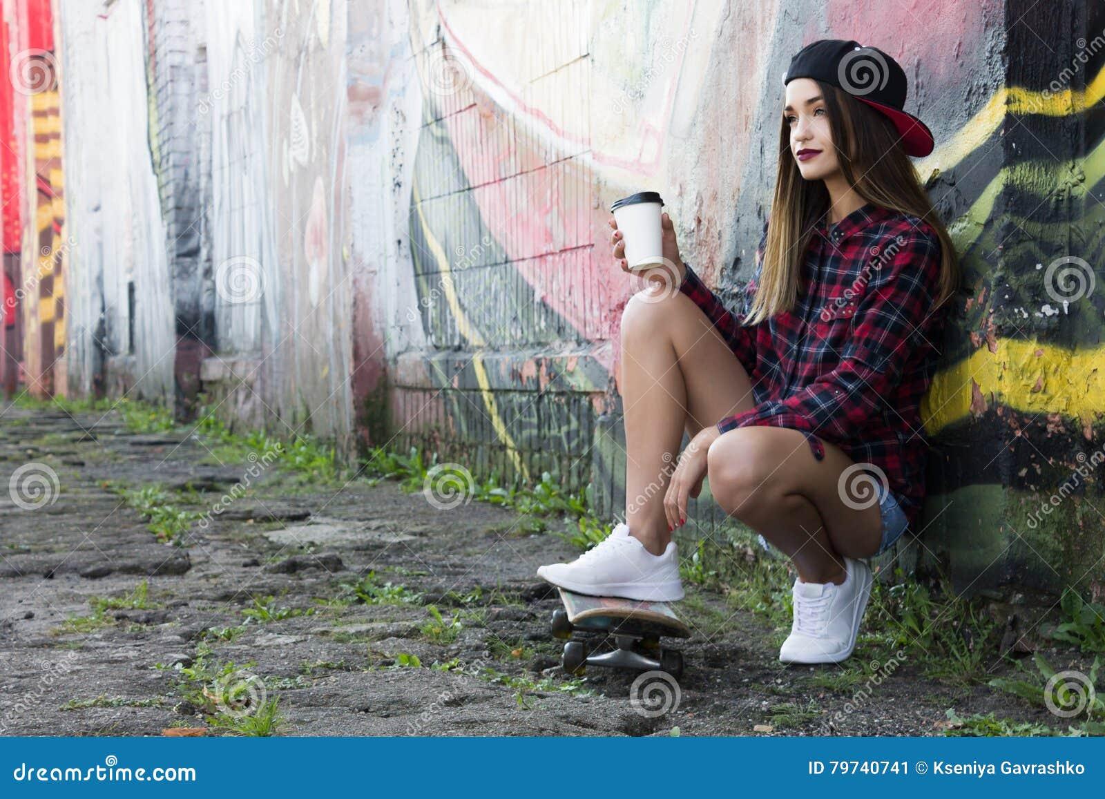 Chica joven hermosa que se sienta en un monopatín Copie el espacio