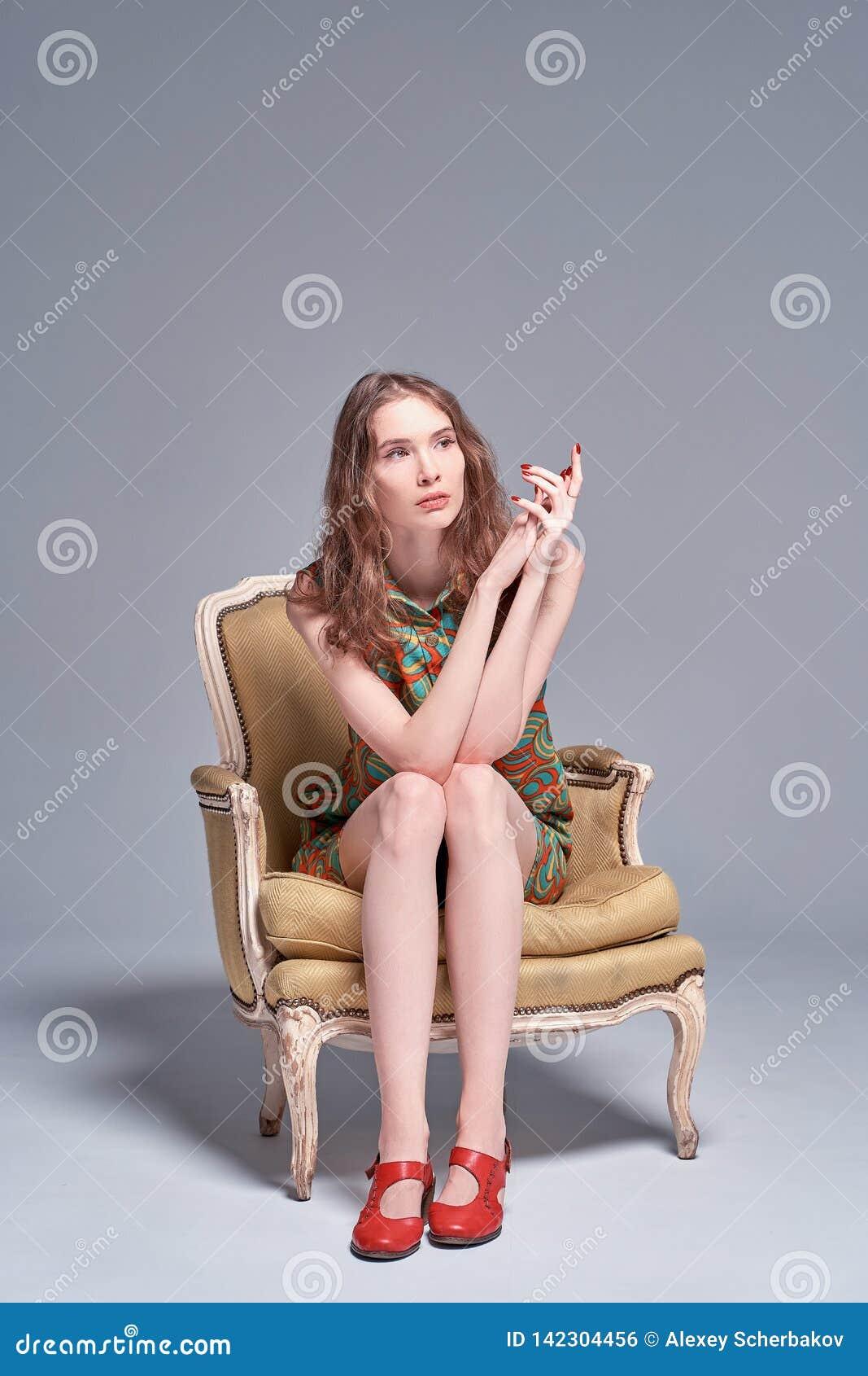 Chica joven hermosa que se sienta en una silla del vintage