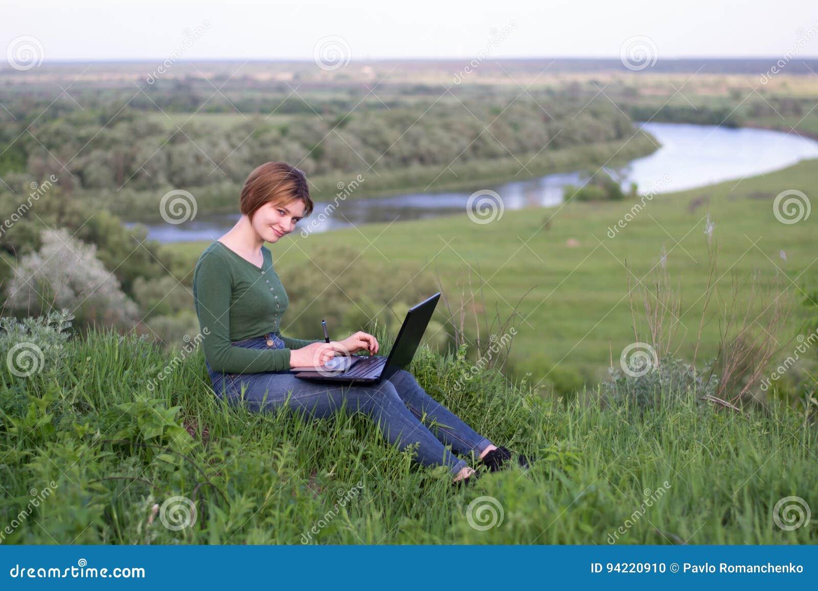 Chica joven hermosa que usa su tableta gráfica que se sienta en la hierba cerca del río