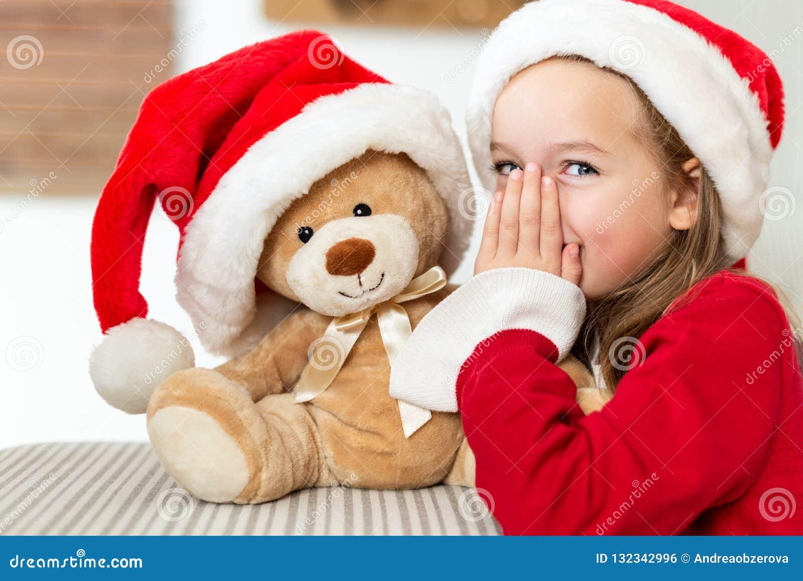 Chica joven linda que lleva el sombrero de santa que susurra un secreto a su juguete del regalo de Navidad del oso de peluche Niñ