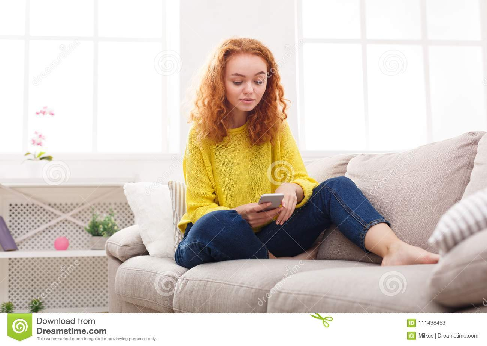 Chica joven pensativa del pelirrojo que manda un SMS en smartphone