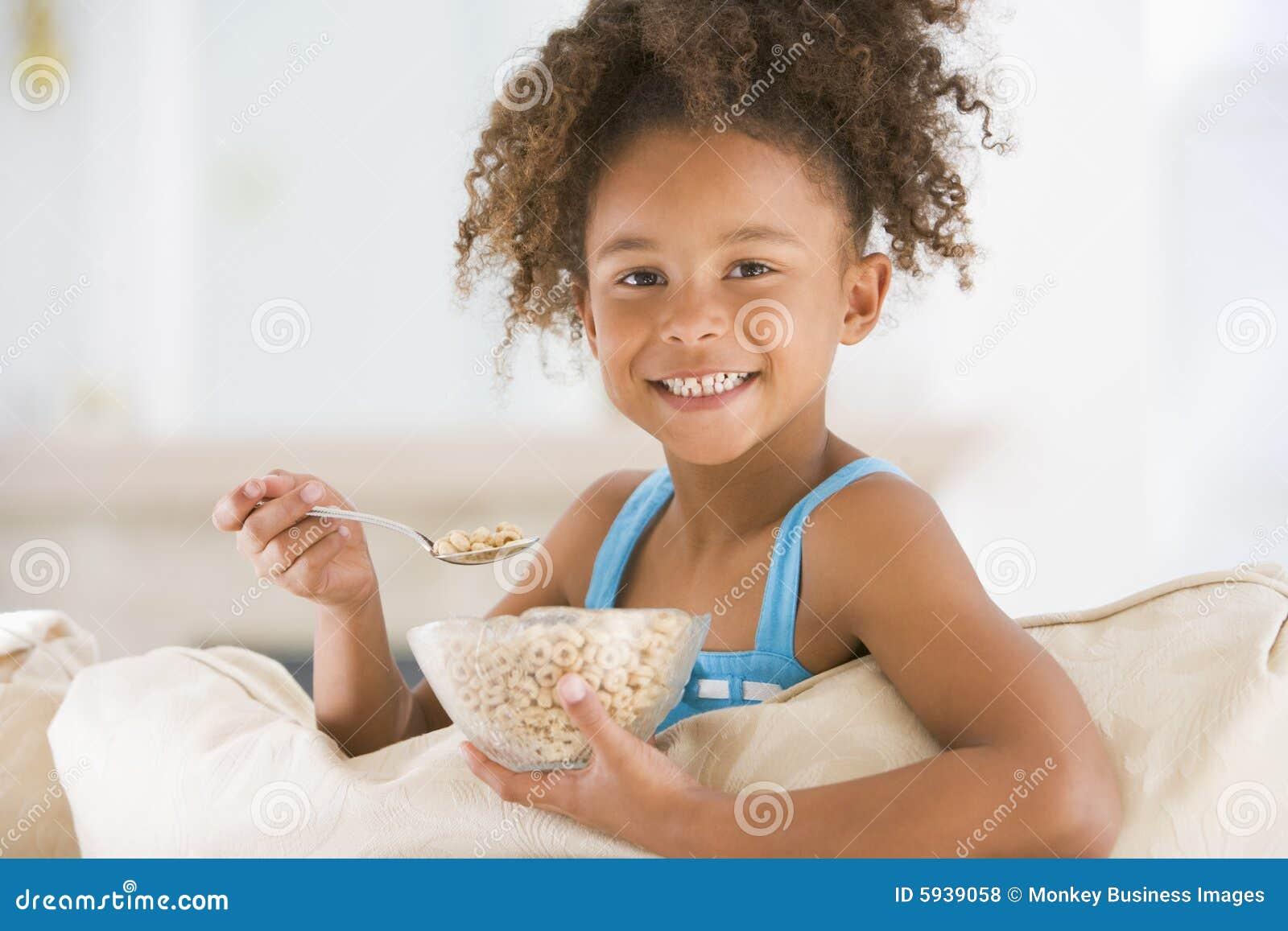 Chica joven que come el cereal en la sonrisa de la sala de estar