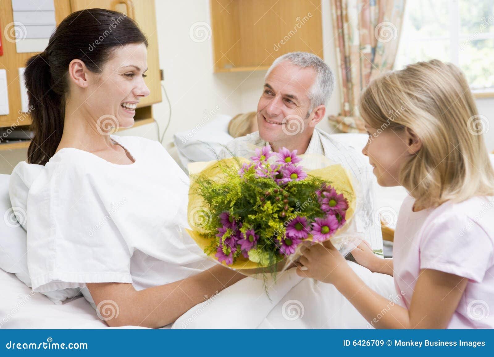 Chica joven que da las flores a la madre en hospital
