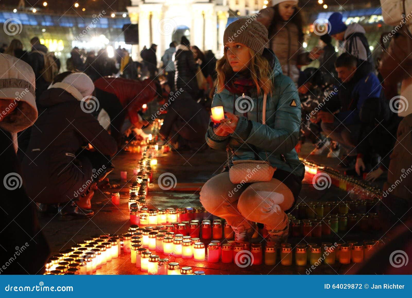 Chica joven que enciende una vela en Kyiv