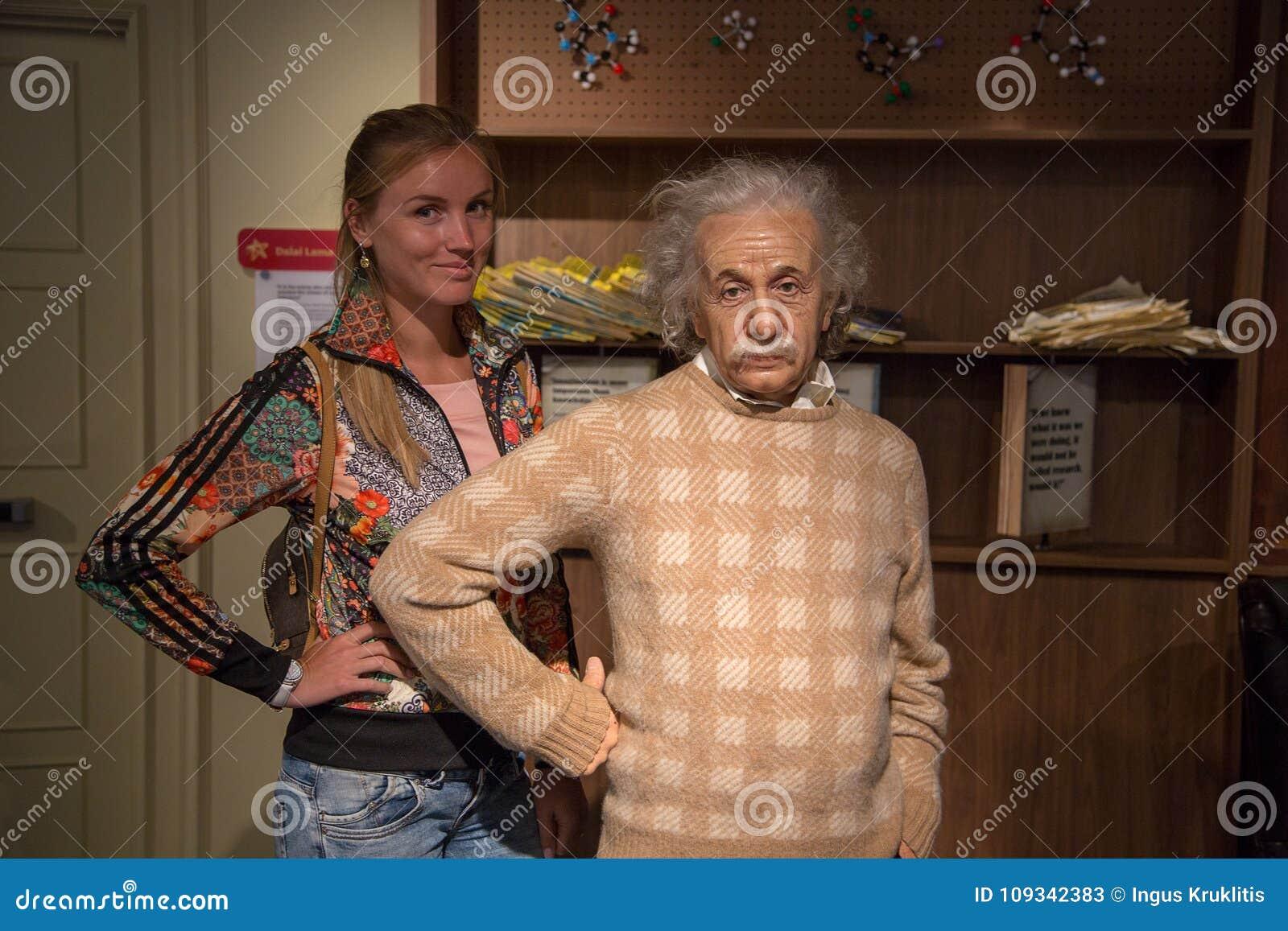 Chica joven que hace una pausa a Albert Einsten en señora Tussauds