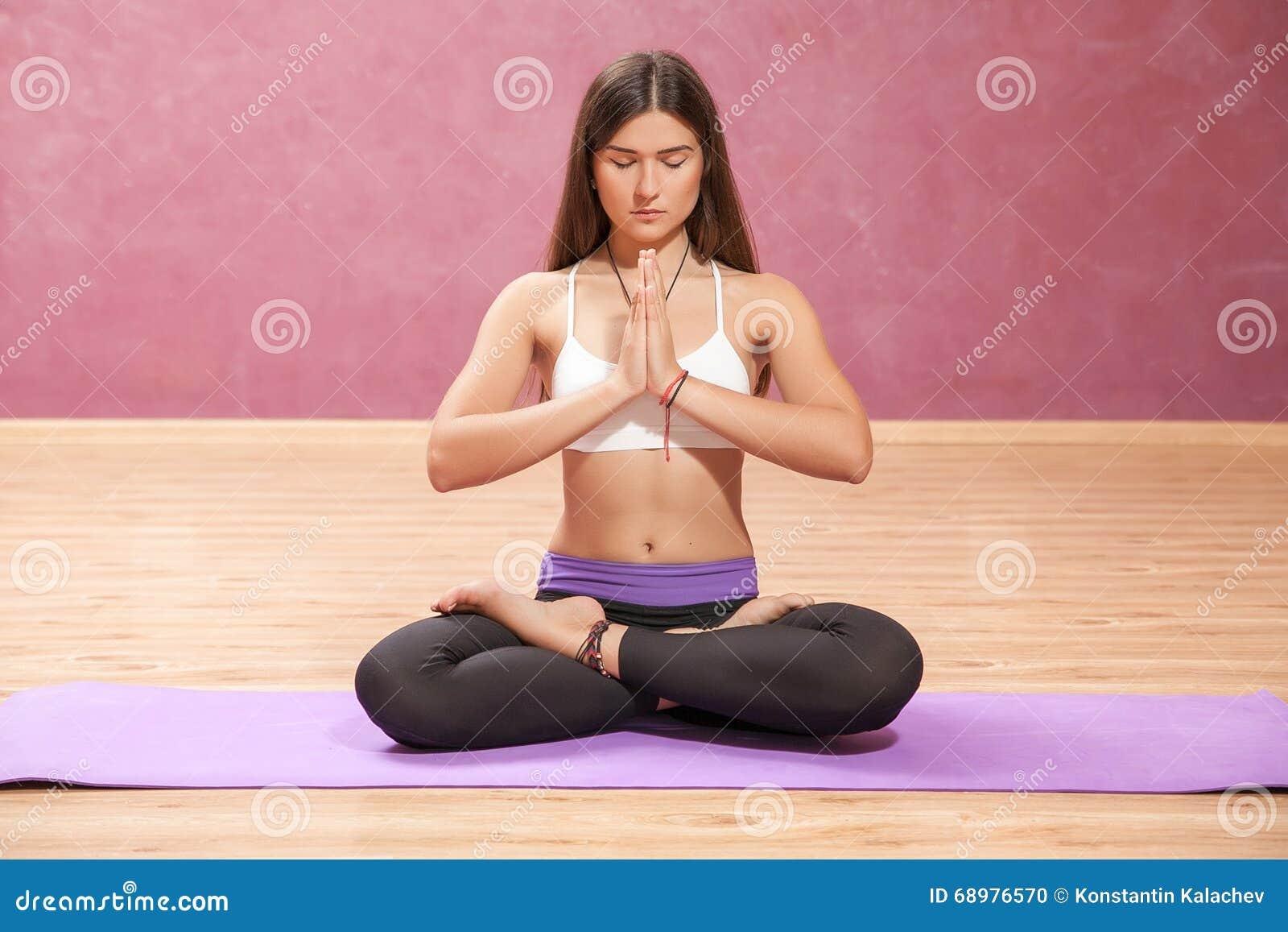 Chica joven que hace yoga en la estera dentro