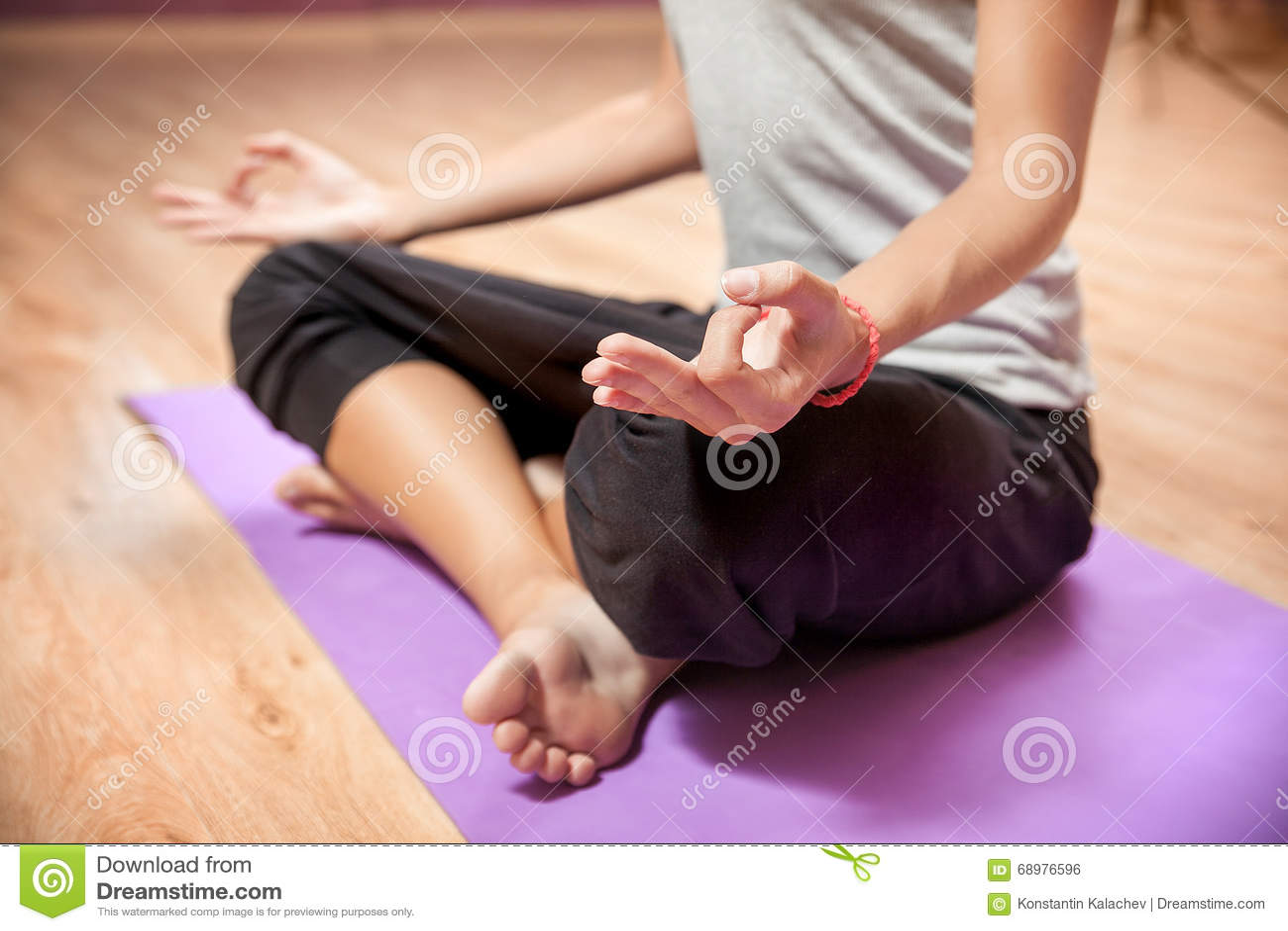 Chica joven que hace yoga en primer de la posición de loto dentro