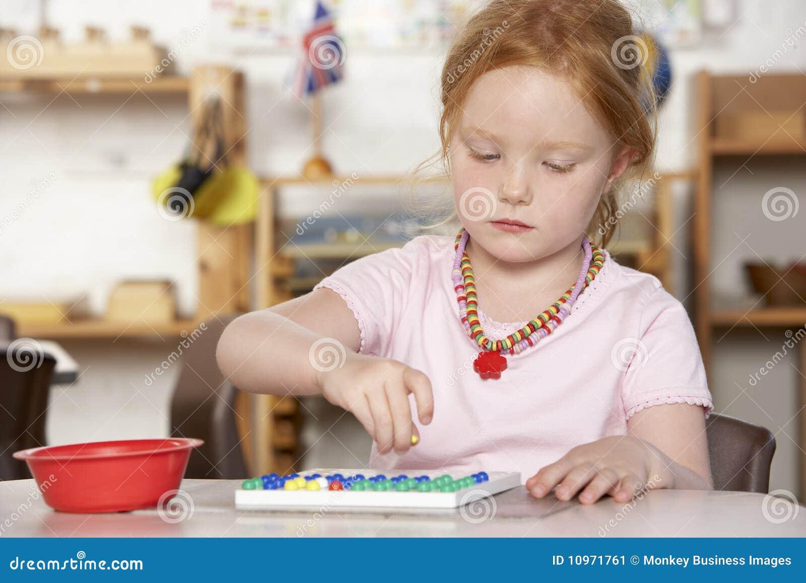 Chica joven que juega en Montessori/el pre-entrenamiento