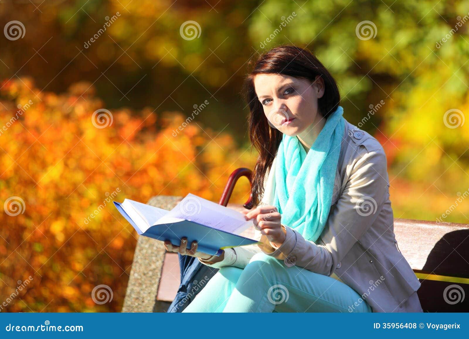 Chica joven que se relaja en libro de lectura otoñal del parque