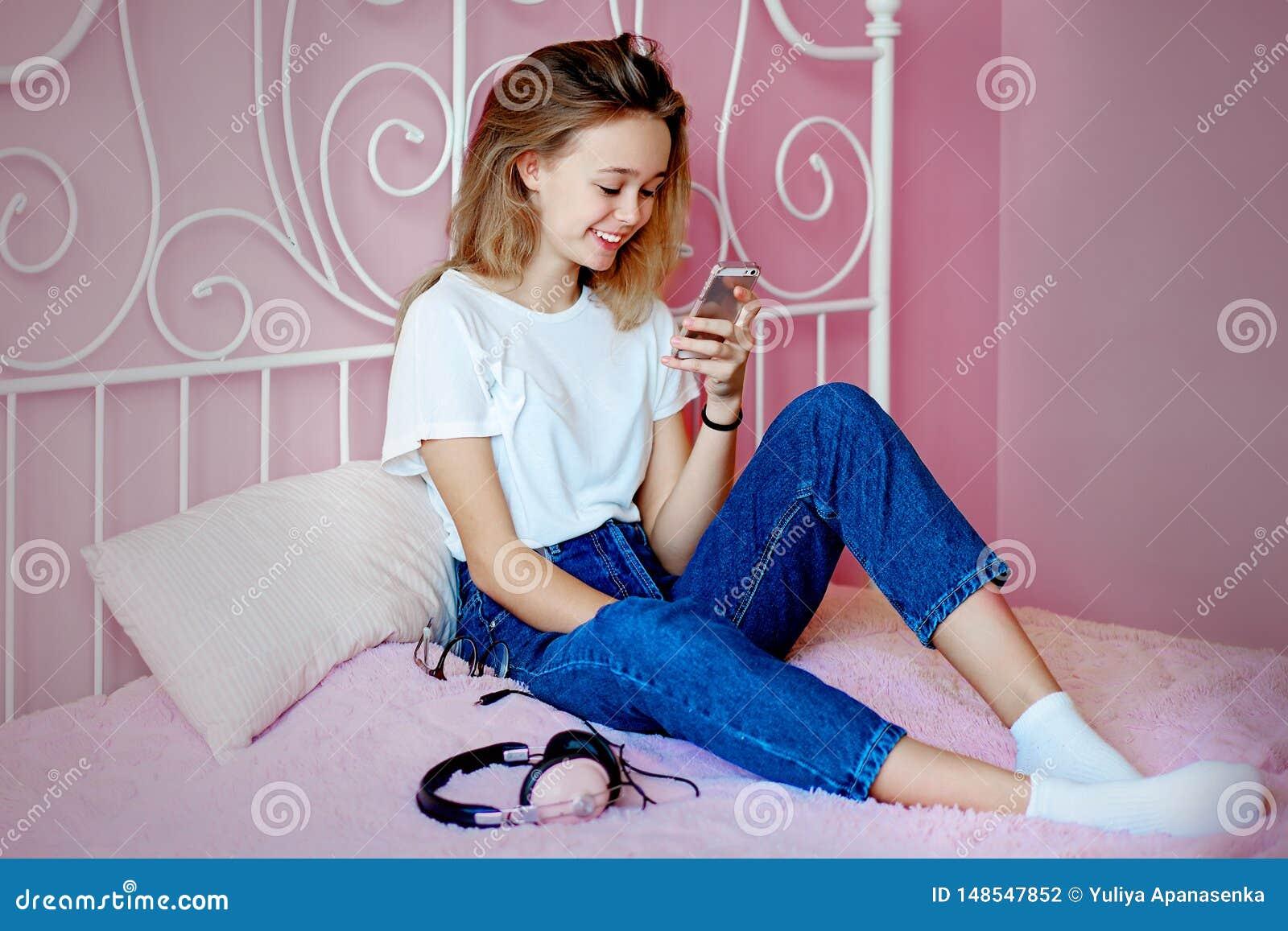 Chica joven que usa el smartphone que se sienta en la cama