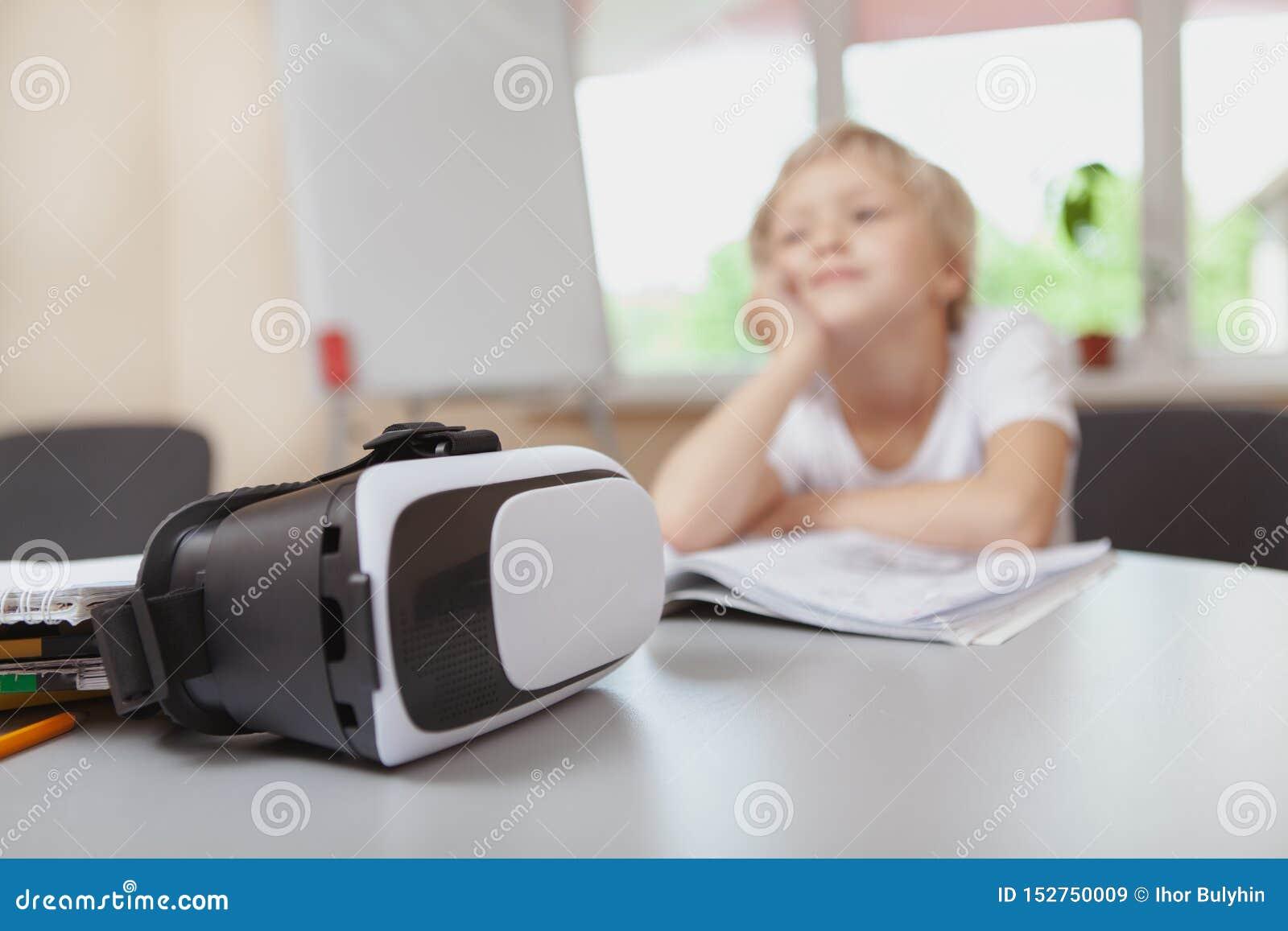 Chica joven que usa las auriculares de la realidad virtual 3d en la escuela