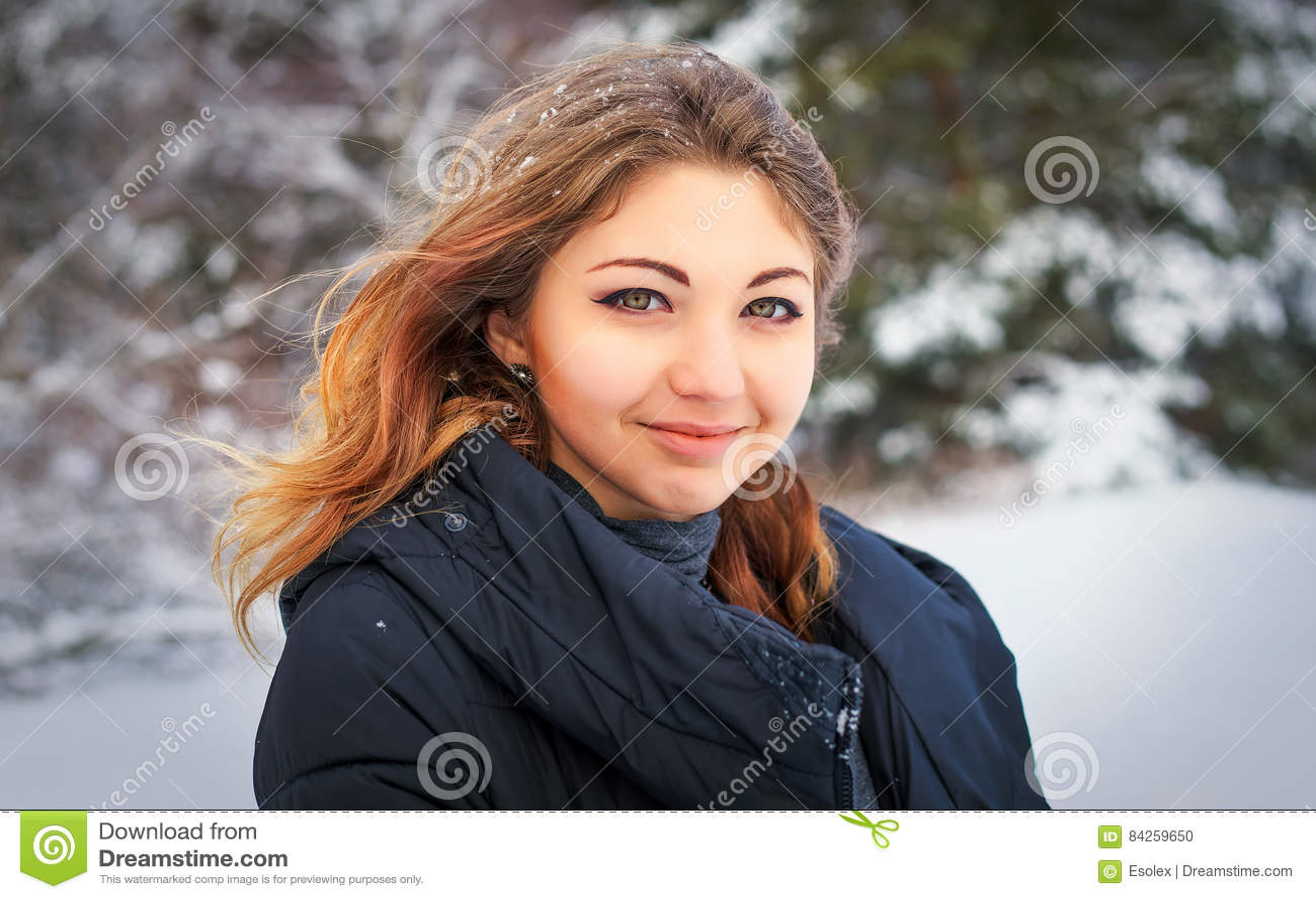 Chica joven sonriente hermosa en el invierno en bosque frío