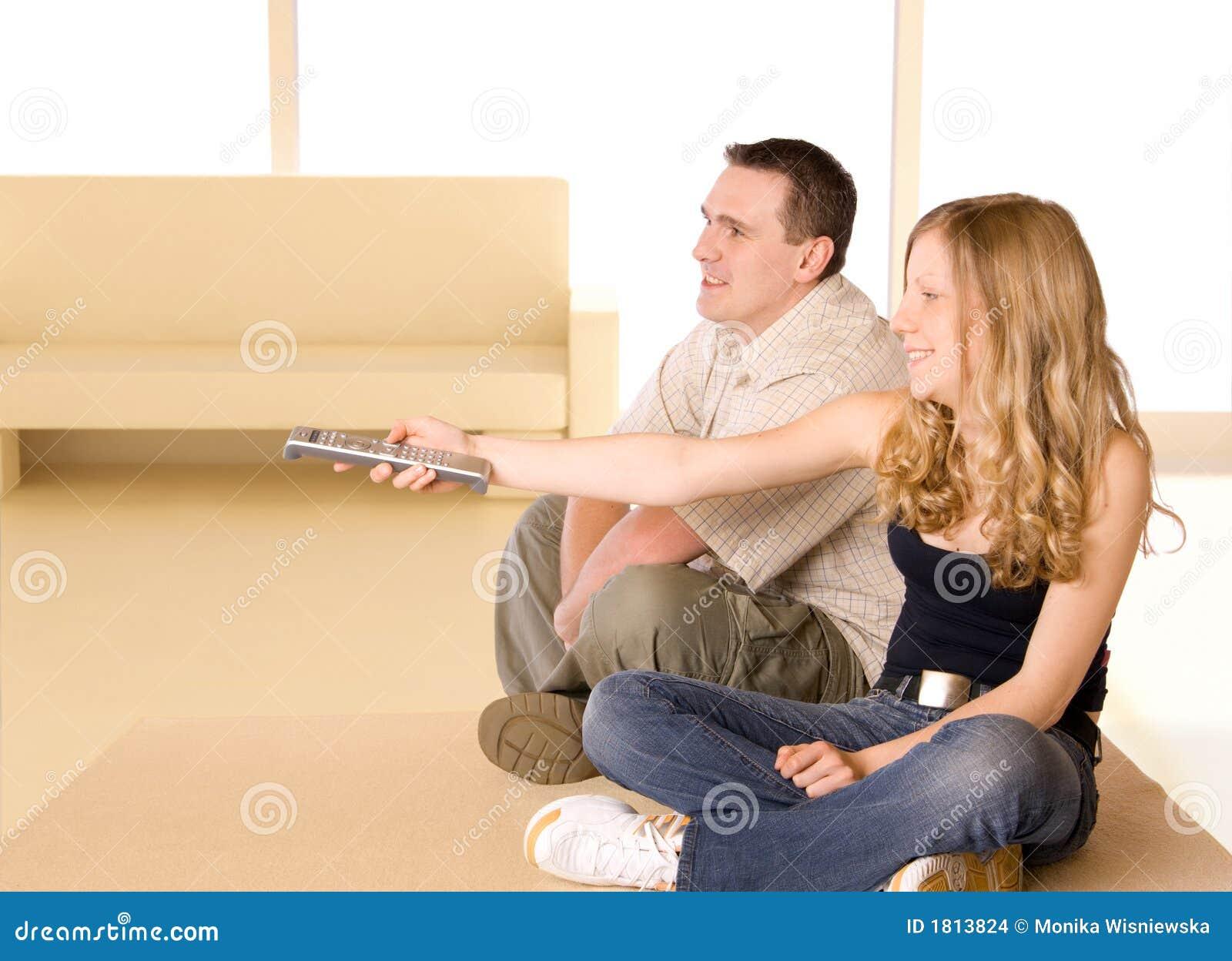 Chica joven y hombre que ven la TV
