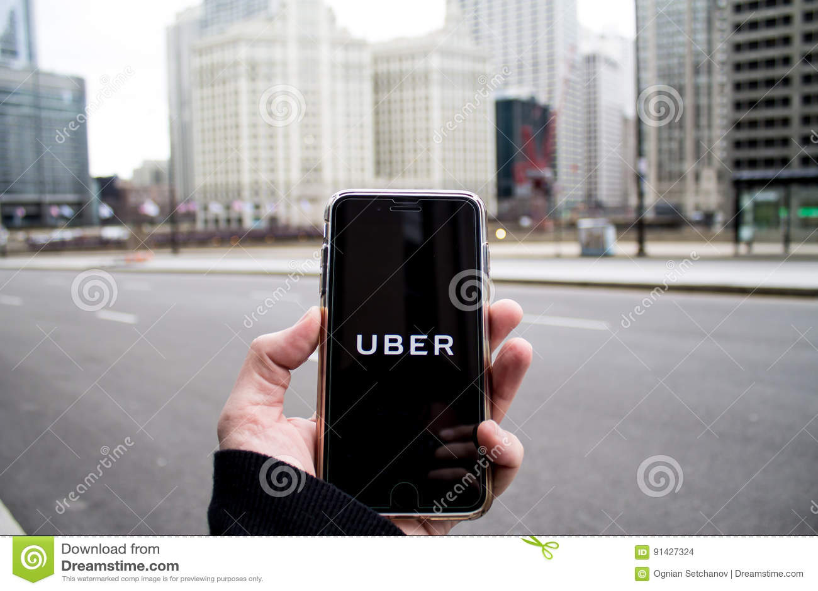 Chicago, IL, EUA, Feb-21,2017, homem que guarda um smartphone com Uber aberto app na cidade para o uso editorial somente