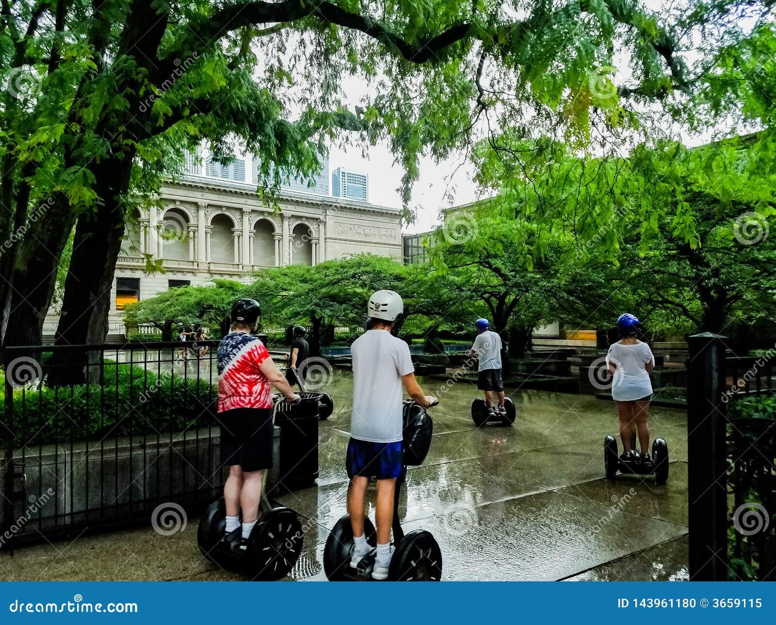 Chicago, Illinois, los E 07 07 2018 Grupo de turistas en viaje de los segways en el parque cerca del museo