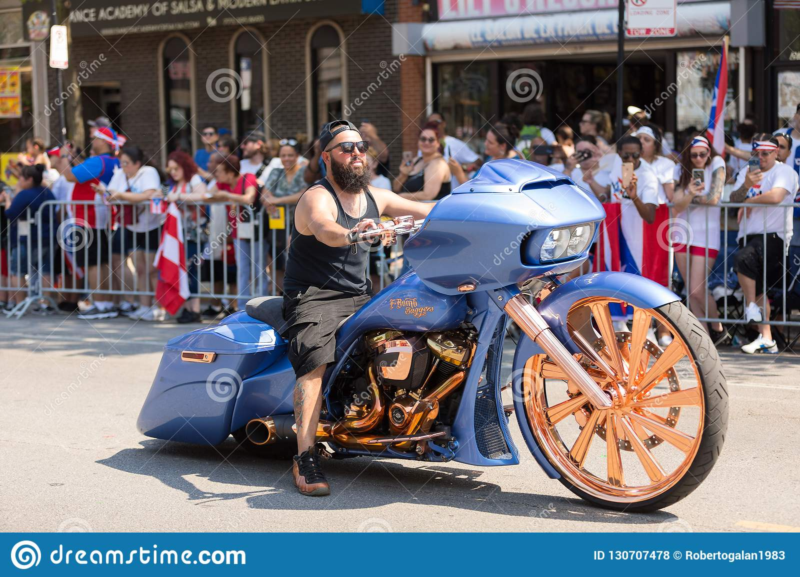 Chicago illinois usa june 16 2018 the puerto rican peoples parade man riding a custom build motorcycle with large wheels and a sticker that says