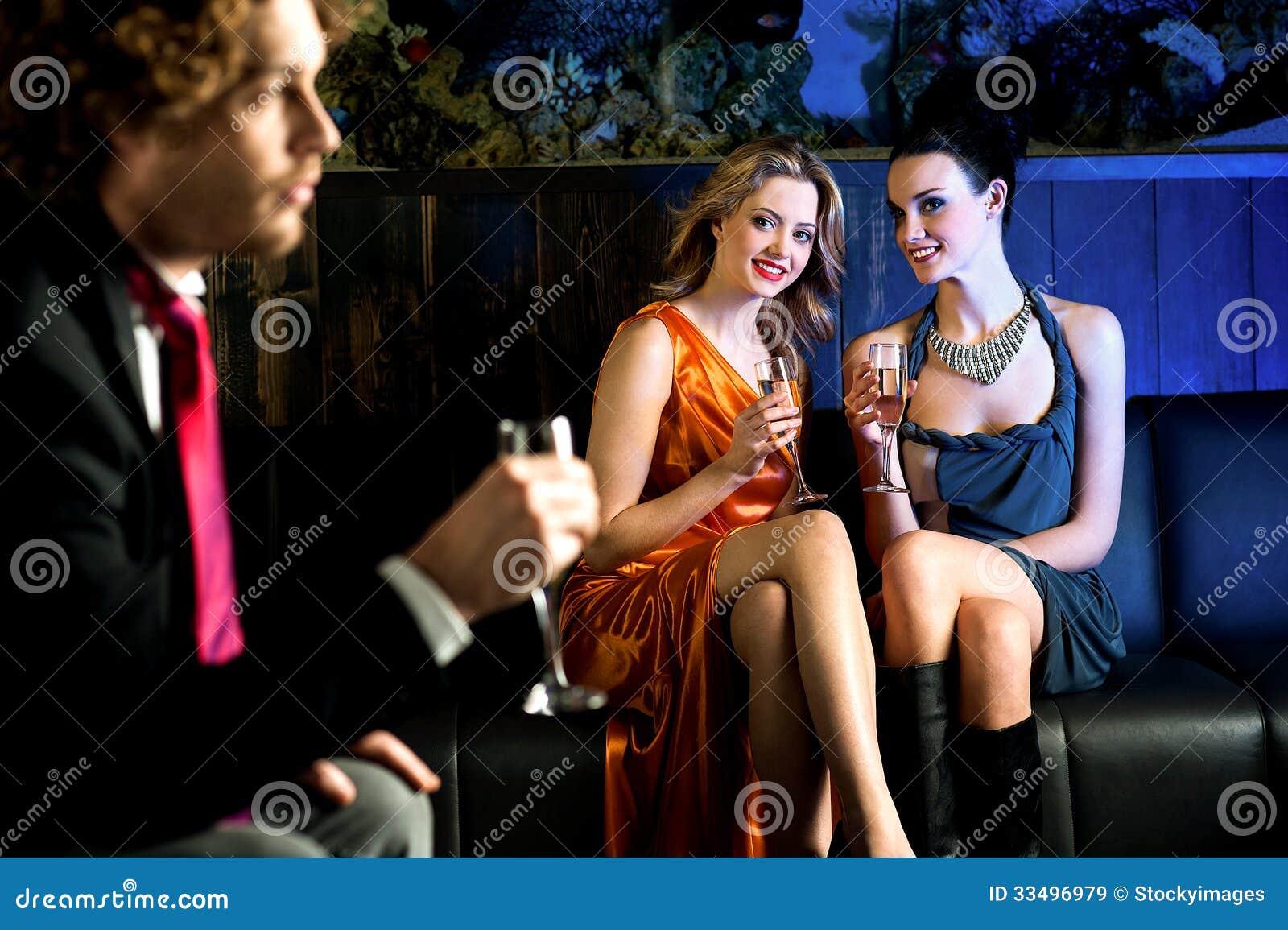 Chicas jóvenes coquetas que miran fijamente el individuo hermoso