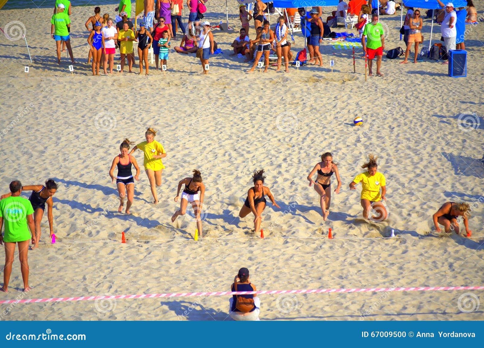 Chicas jóvenes que compiten con en la playa del verano