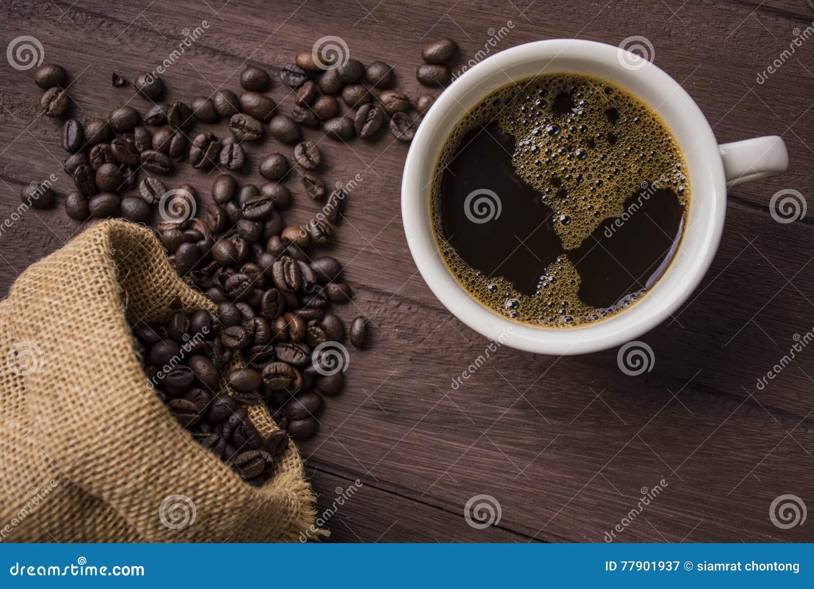 Chicchi della tazza e di caffè di /Coffee di vista superiore sulla tavola di legno