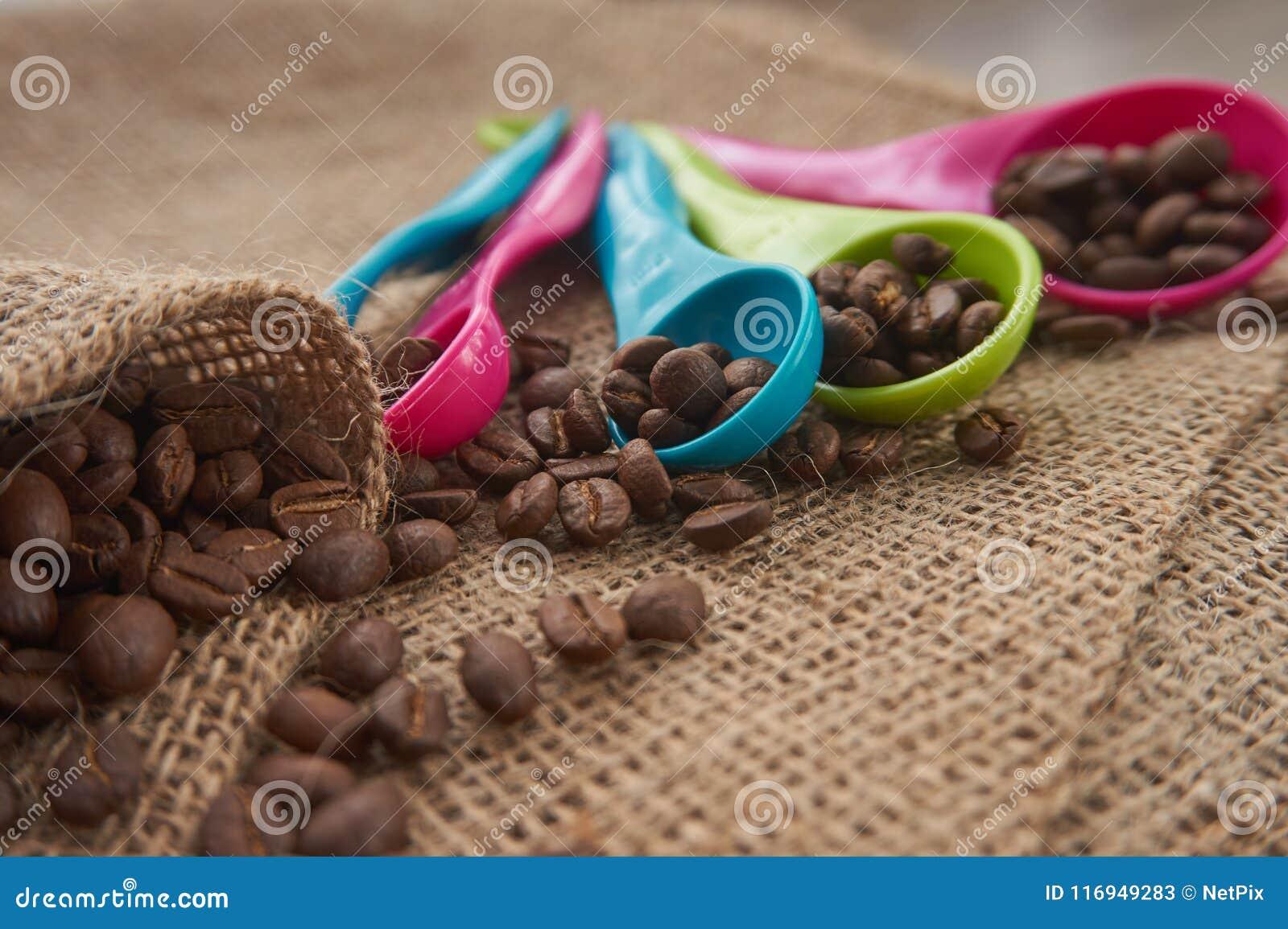 Chicchi di caffè arrostiti, di dosatore della dose sul sacco della iuta