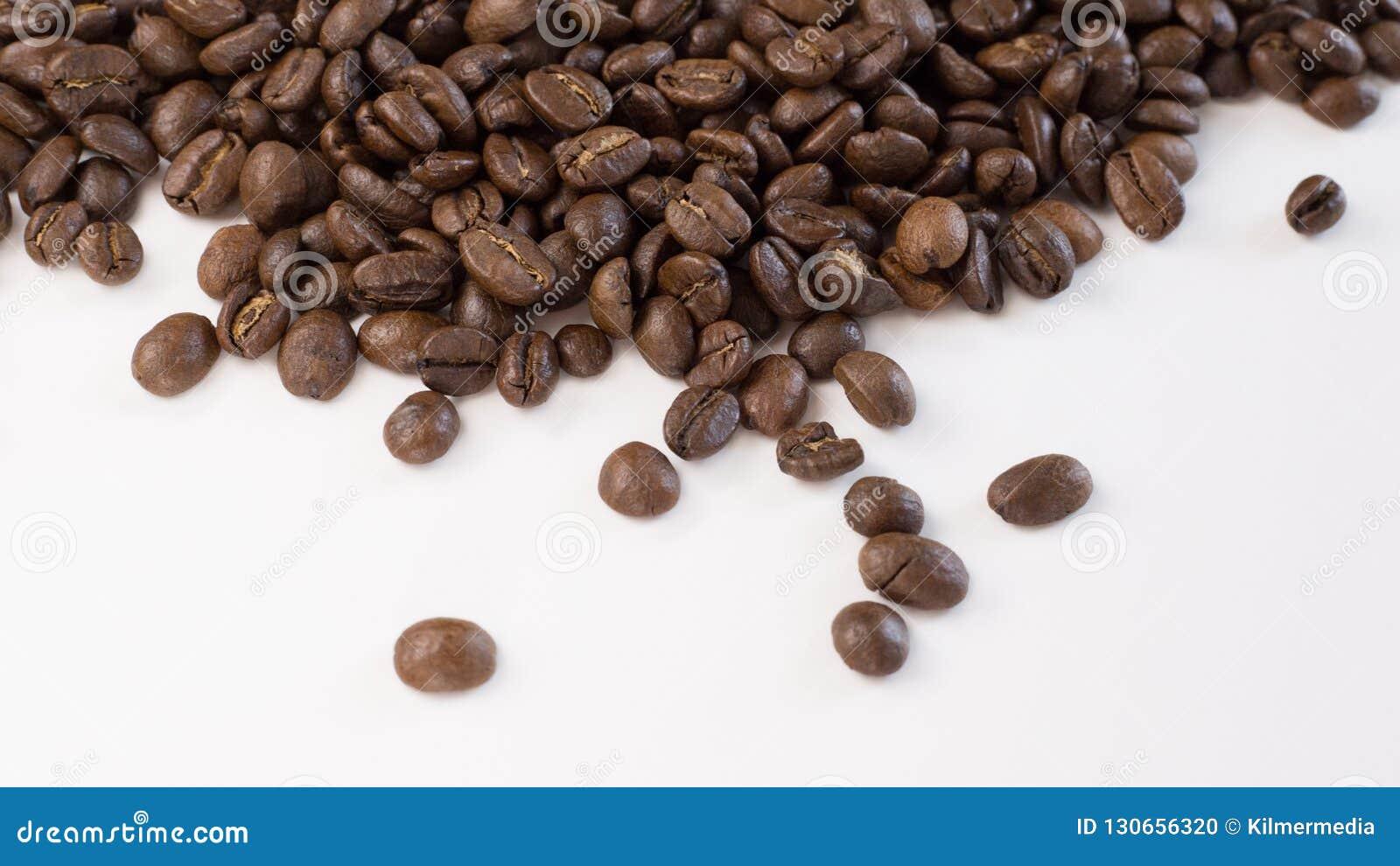 Chicchi di caffè arrostiti sparsi su un fondo bianco