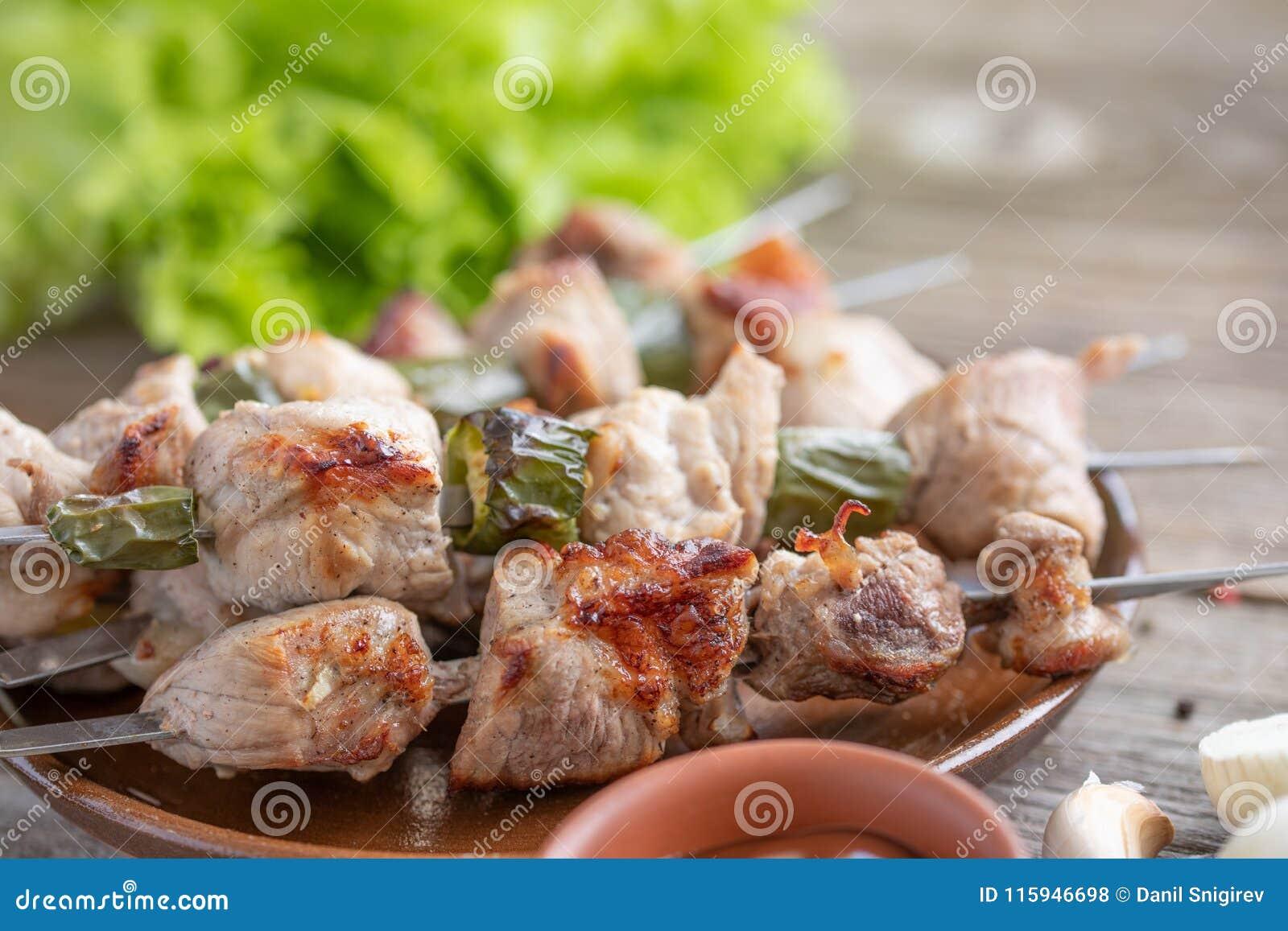 Chiche-kebab sensible du porc cuit sur un feu ouvert et des feuilles fraîches de laitue la vie toujours sur un fond en bois Plan
