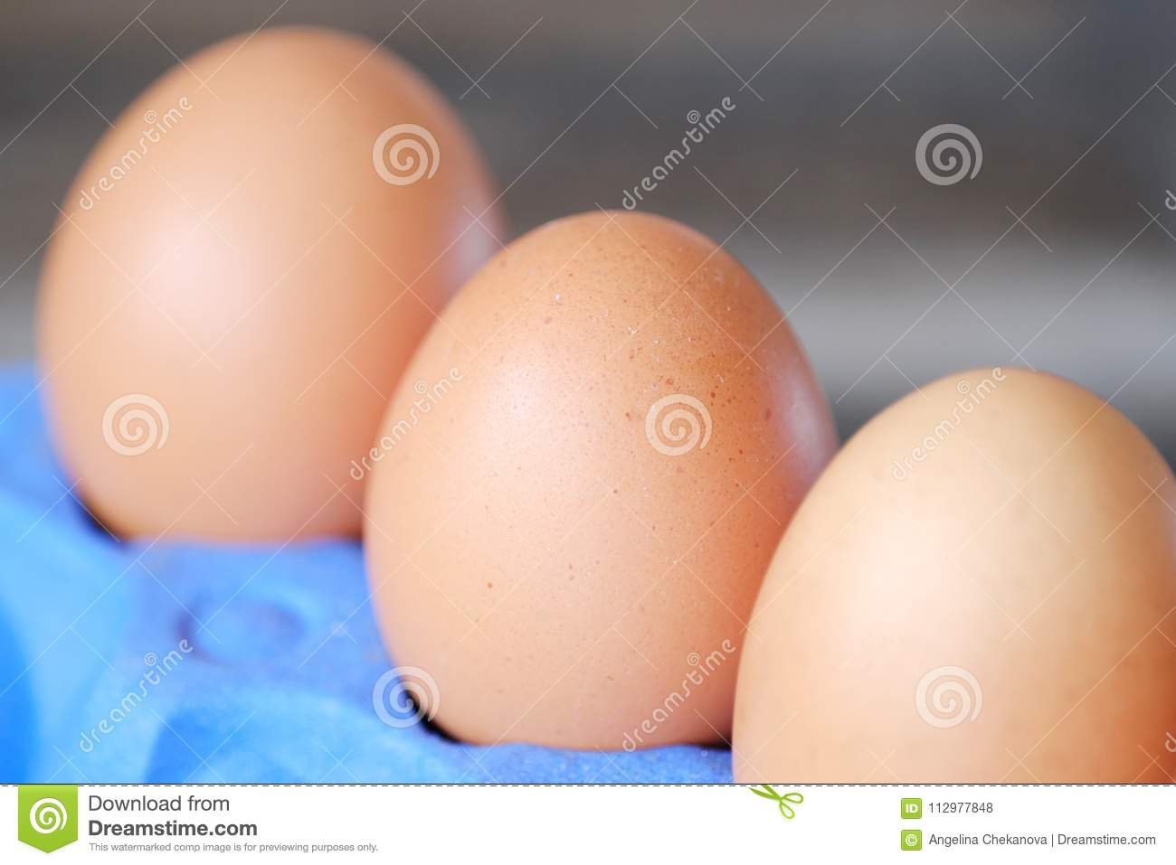 Chicken eggs in the purple package on the table