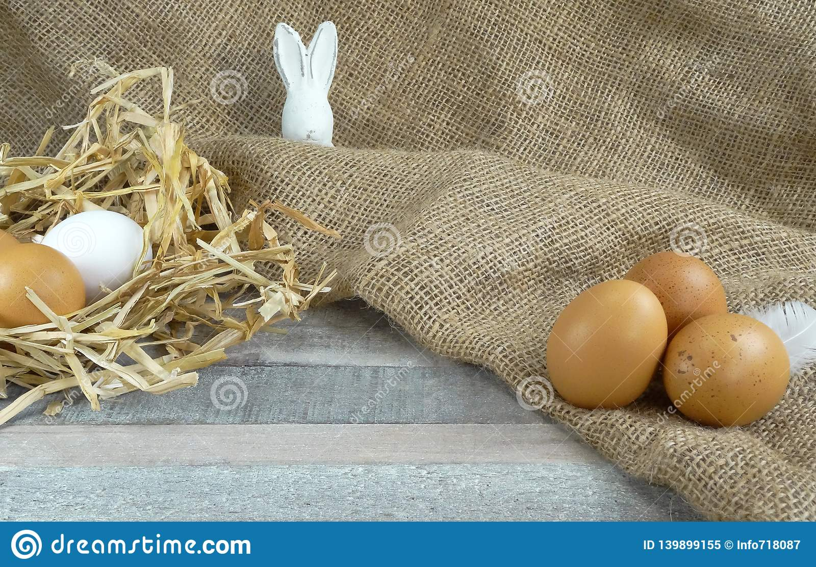 Chicken eggs in straw nest witheaster bunny at burlap over wooden background