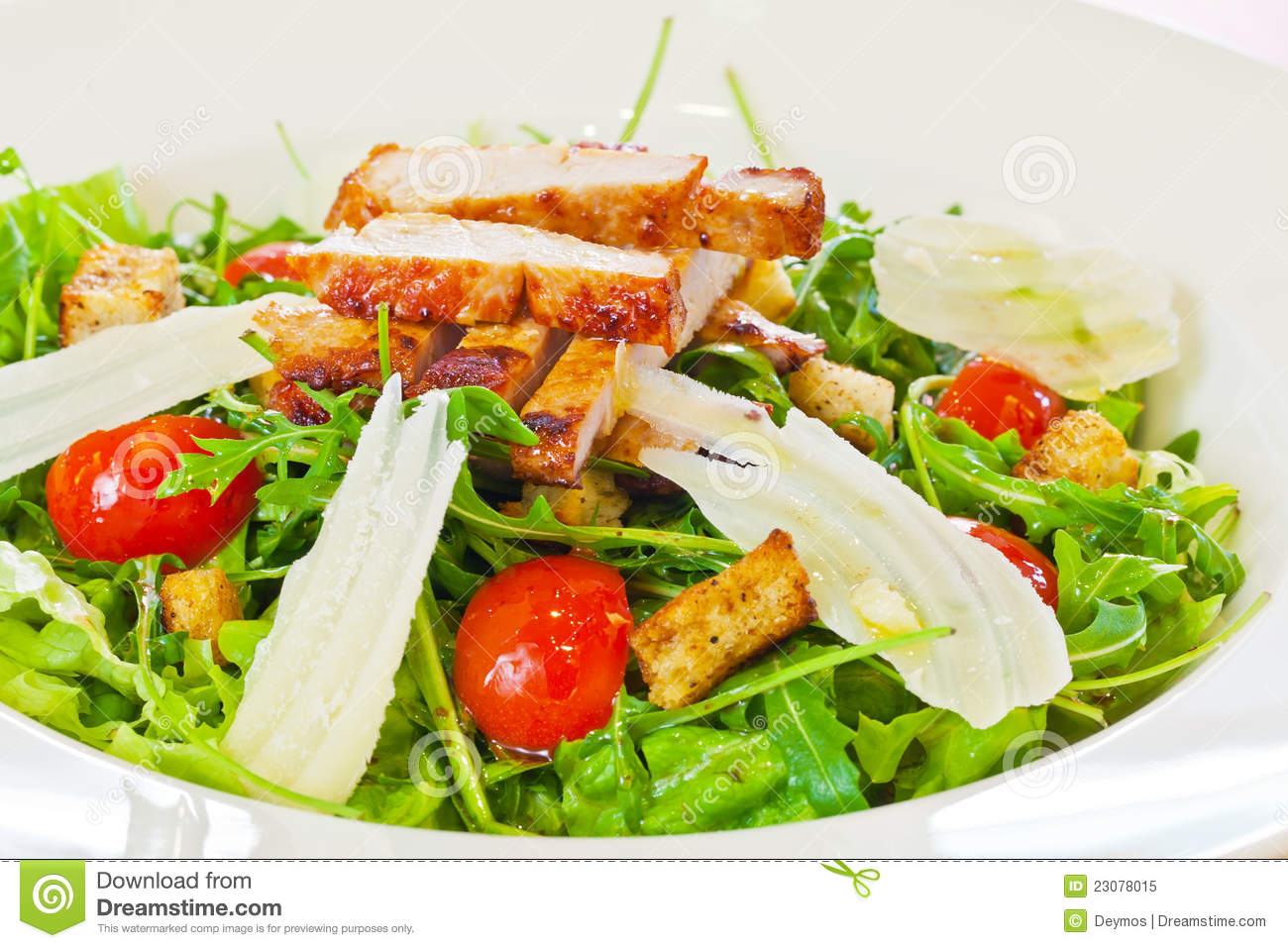 Chicken salad with tomatoes, arugula and bread croutons in the white ...