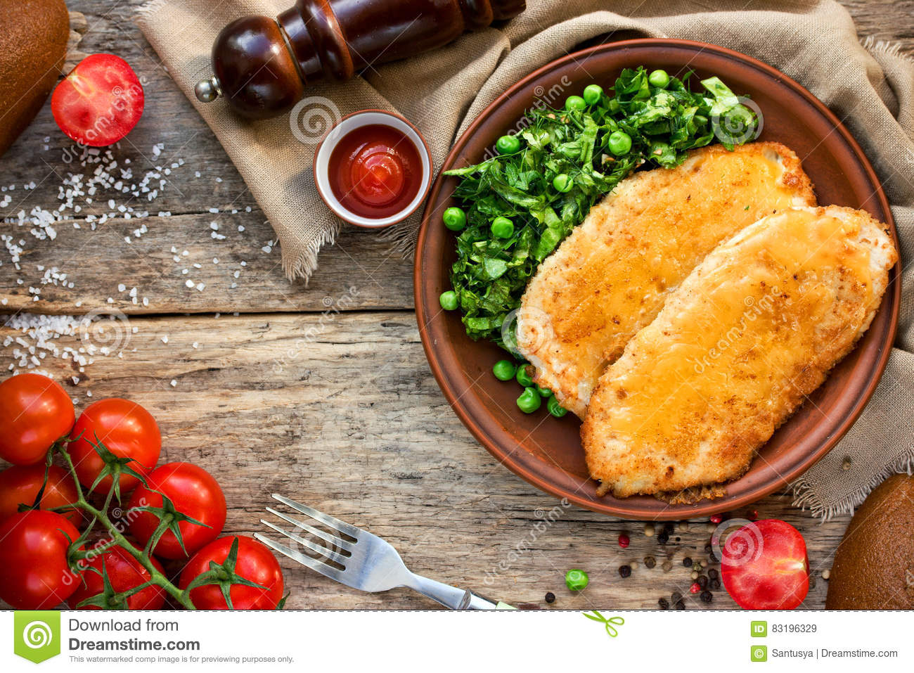 Chicken schnitzel with or cordon bleu with green salad and cherry tomatoes in a rustic style on the old wooden background