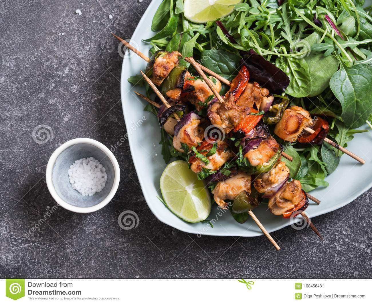 Chicken on skewers on oval dish and fresh salad plate with mixed greens with chicken on skewers