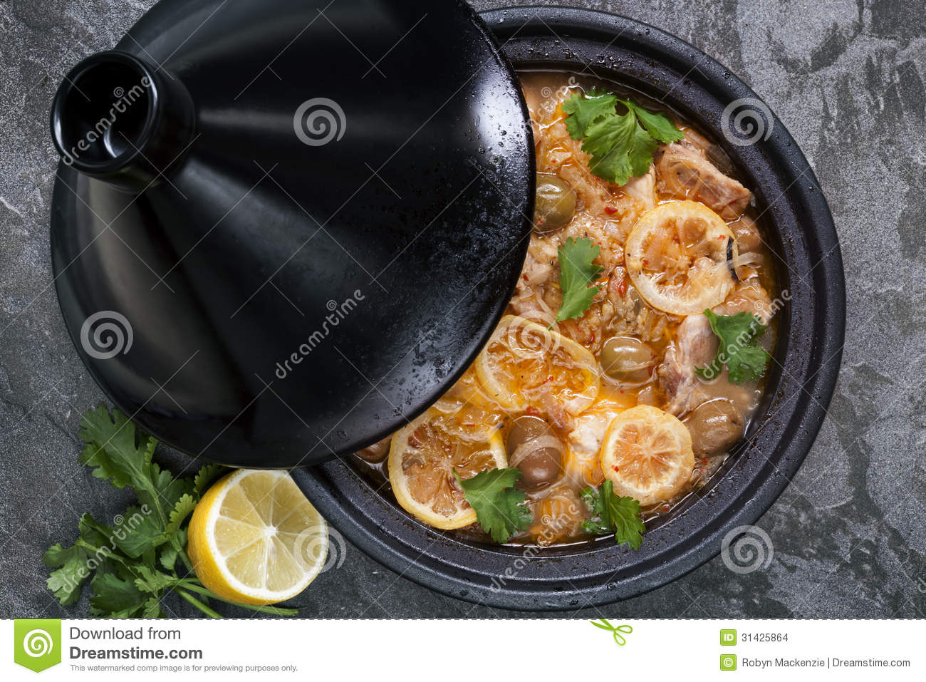 Chicken cooking in traditional tagine. With lemons, green olives and ...