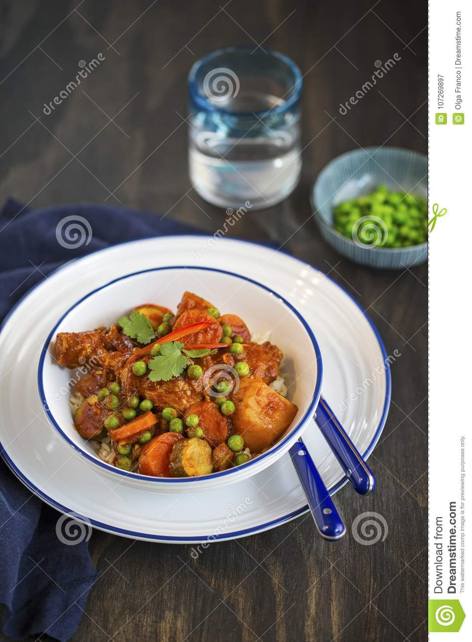 Chicken and vegetable stew in tomato sauce served on rice
