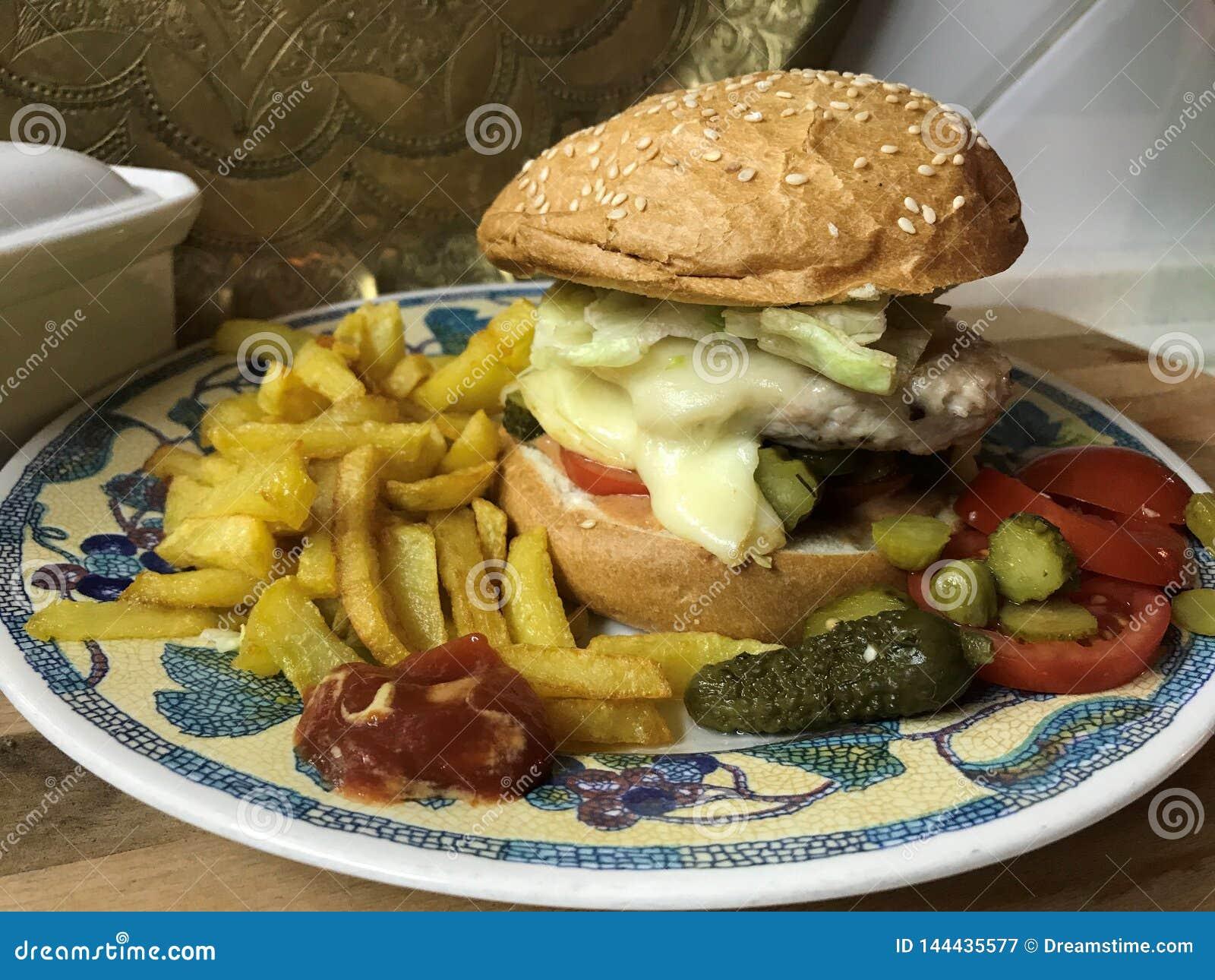 Chickenburger z kurczaka hamburgerem, warzywami, Dijon opatrunkiem i francuzów dłoniakami,