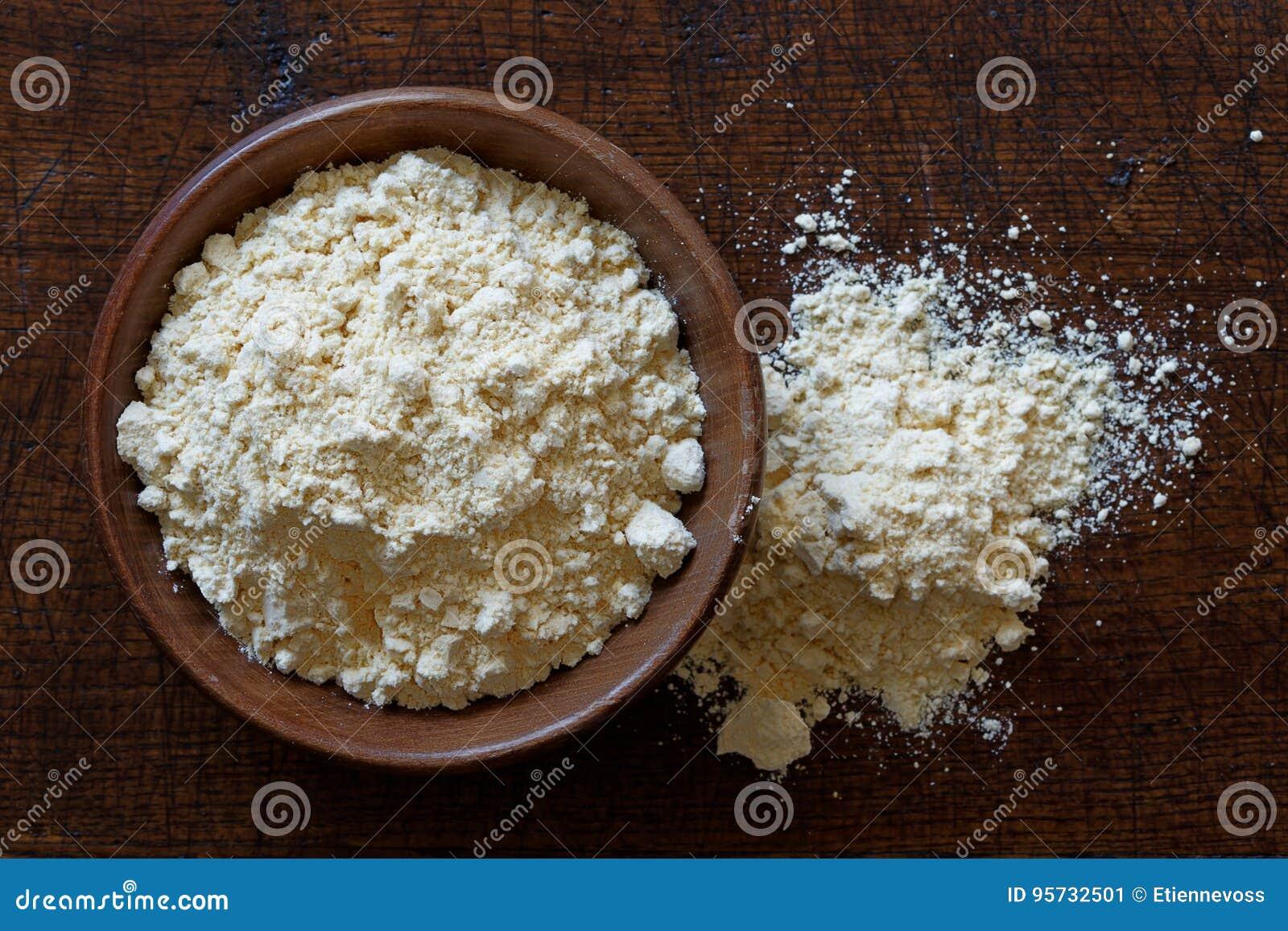 Chickpea mąka w ciemnym drewnianym pucharze odizolowywającym na ciemnego brązu drewnie f