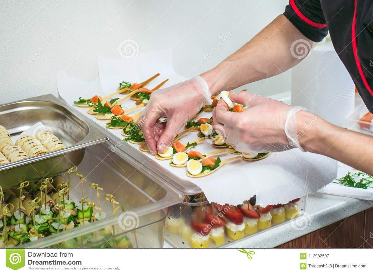 Chief at kitchen prepareing delicates, appetizers. Catering service. Closeup shoot of hands.