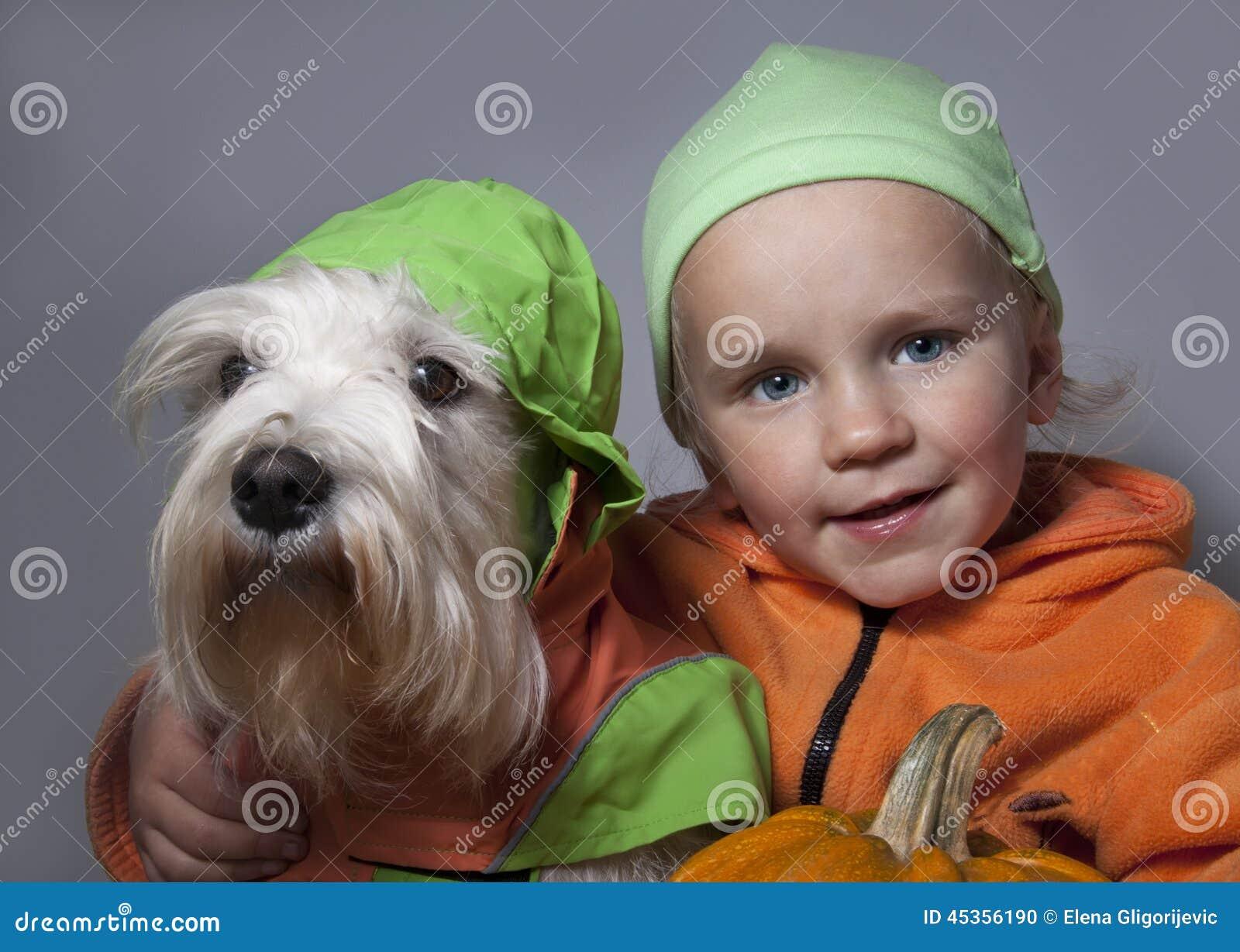 Chien mignon et enfant portant un potiron de Halloween