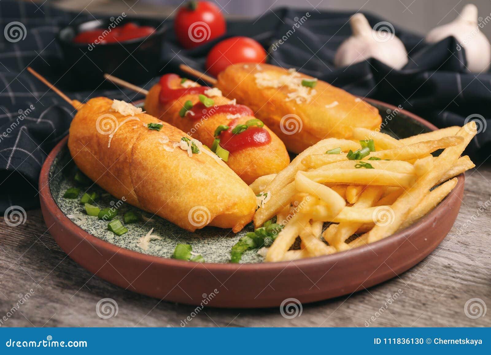 Chiens de maïs savoureux avec le plat de ketchup