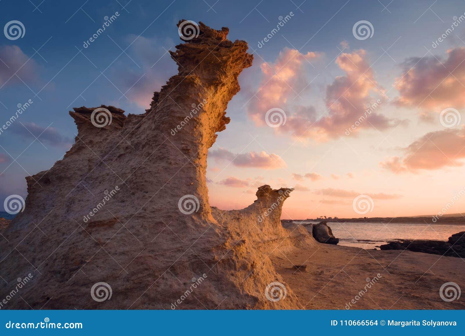 Chiffre de Sandrock à la lumière de lever de soleil sur une plage rocheuse Chypre du nord
