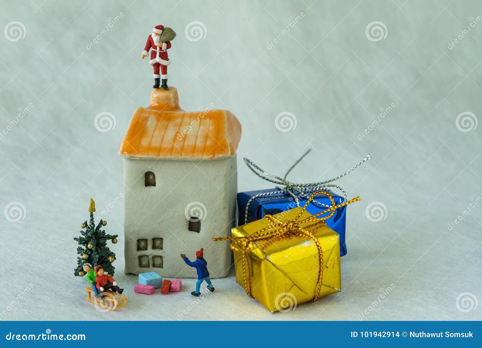 Chiffre miniature le père noël se tenant sur la cheminée et le childr de toit