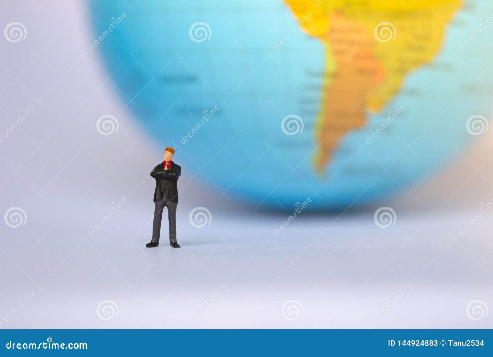 Chiffres de petit homme d affaires se tenant sur le tournant sur le fond de la terre