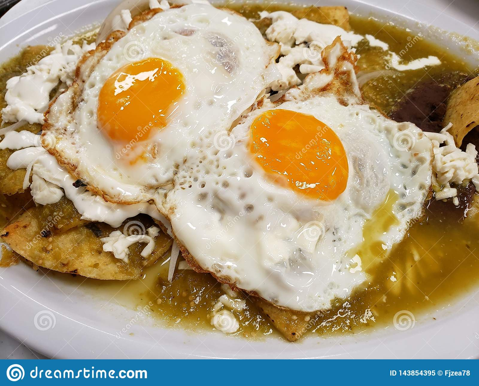chilaquiles dish with fried egg for lunch, traditional mexican food