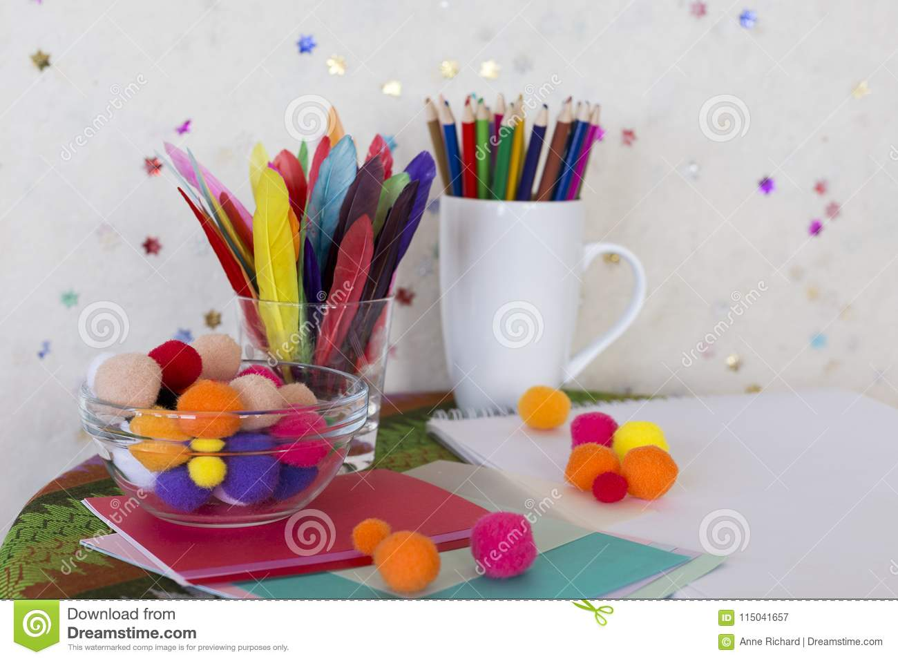 Child arts and craft work station with colored pencils, colourful feathers, pom poms and paper