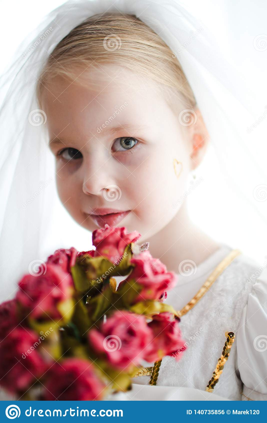 Child as s bride posing with bouquet - small golden heart on cheek