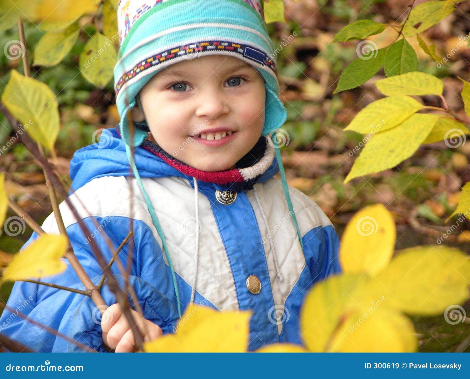 Child and autumn leaves around